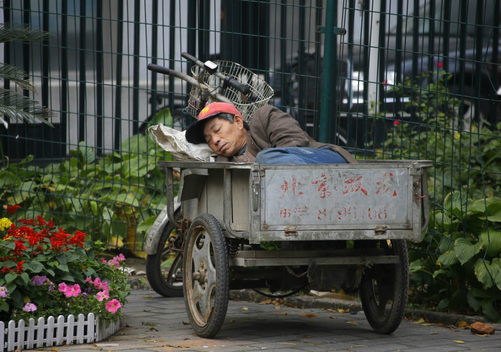 A man takes a nap in the back of his cycle cart at the gate of the Tayuan Diplomatic Office Building in Beijing